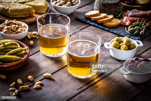 beer and tapas shot on rustic wooden table - salumeria stock photos and pictures