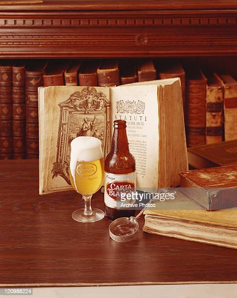 Beer bottle and glass in front of open book