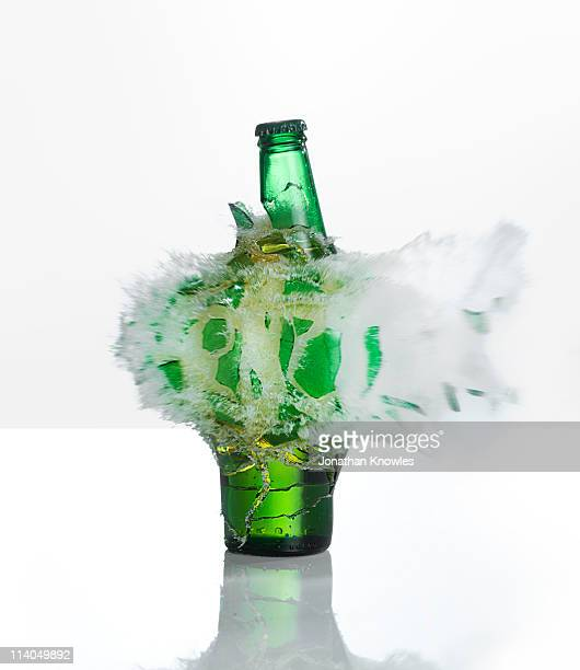 A beer bottle exploding on  a white background