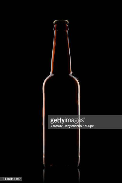 beer bottle isolated on black - beer bottle stock pictures, royalty-free photos & images