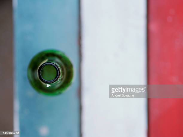 Beer bottle on colorful table seen from above