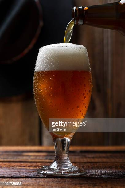 beer bottle pouring beer into beer glass_1 - ian gwinn - fotografias e filmes do acervo