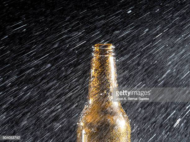 Beer bottle sprayed with water droplets