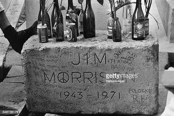 Beer bottles and flowers on the grave of American singer Jim Morrison in Père Lachaise Cemetery Paris France July 1990
