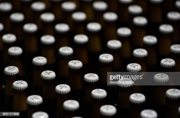 Beer bottles with crowned caps are pictured on the conveyor belts of a filling plant in the Veltins brewery in MeschedeGrevenstein western Germany on...