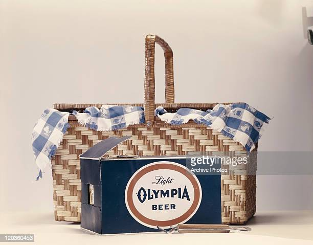 Beer box beside basket on white background, close-up