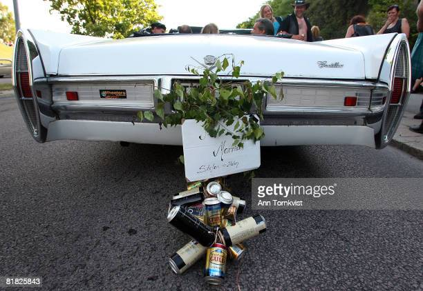 Beer cans hang on the 'Just Married' sign of a car as the couple takes part in a mass drivein wedding with over 50 couples during Power Big Meet on...