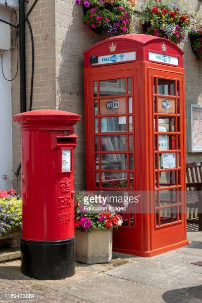Beer Devon England A Royal Mail postbox and a former telephone box used as a book library and WiFi station both newly painted in bright red