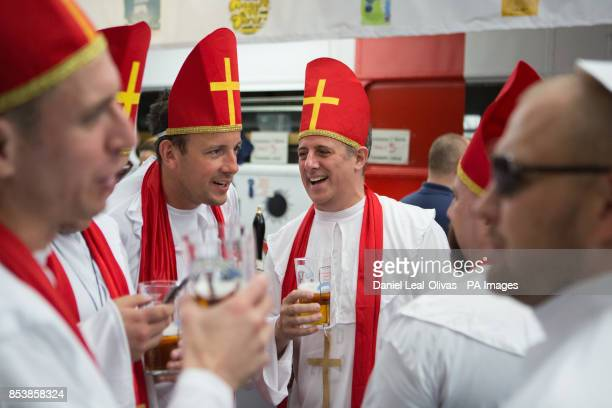 Beer drinkers dressed as priests enjoy the Great British Beer Festival at Olympia London where Prince Harry made an unofficial visit yesterday