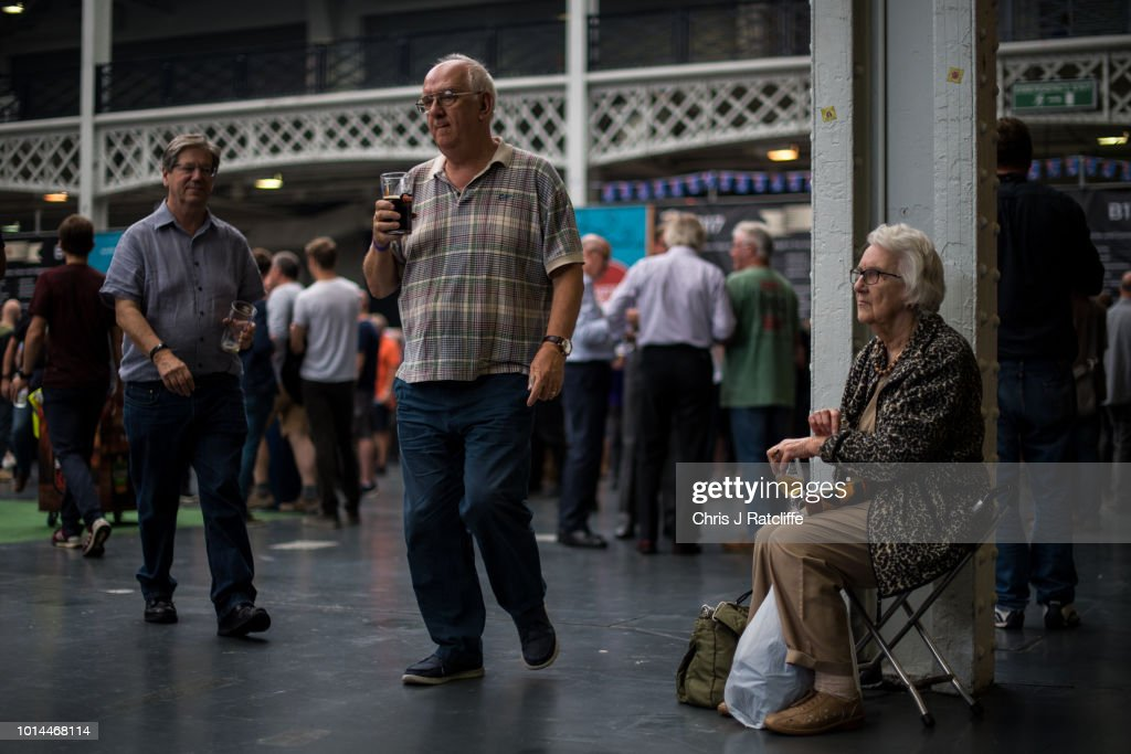 A beer enthusiast walks sits on a stool during the Great British Beer Festival at Olympia Exhibition Centre on August 10, 2018 in London, England. The five day festival showcases over 900 real ales and craft beer and is organised by Campaign for Real Ale group CAMRA.