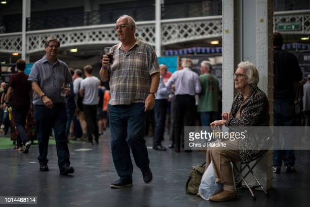 A beer enthusiast walks sits on a stool during the Great British Beer Festival at Olympia Exhibition Centre on August 10 2018 in London England The...