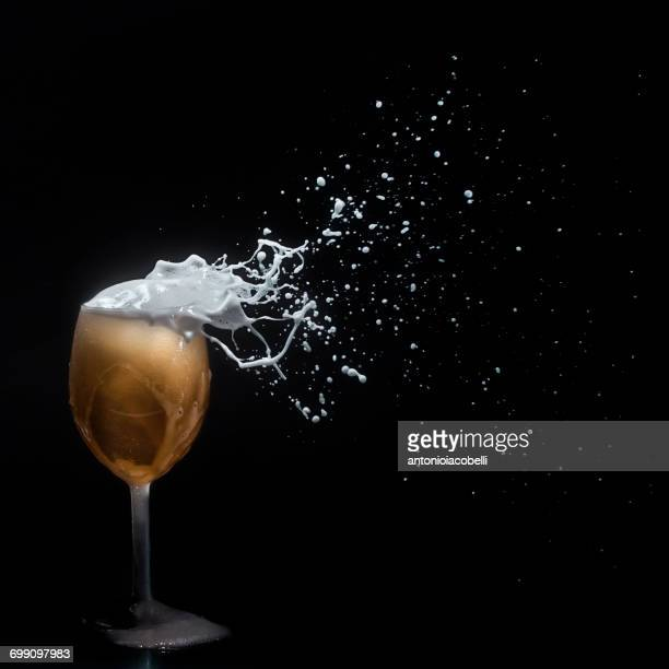 Beer foam blowing off a wine glass