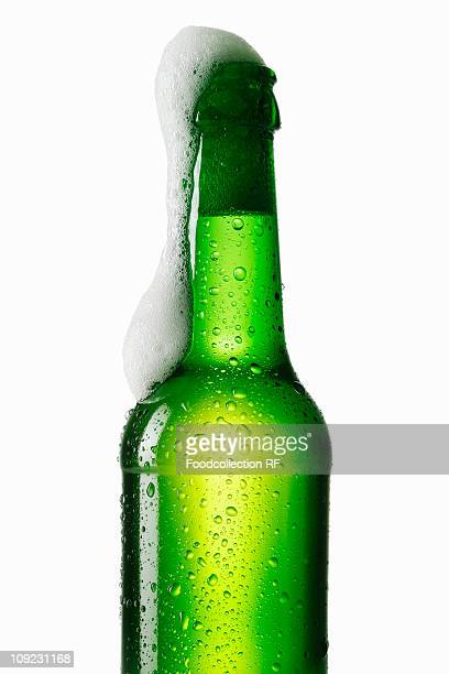 Beer frothing out of green bottle, close-up