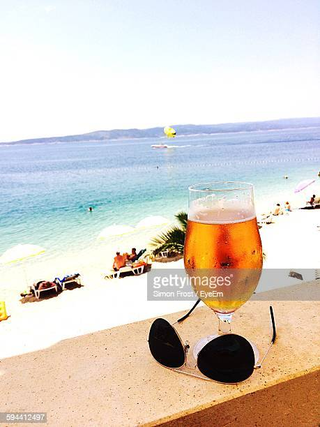 Beer Glass And Sunglasses On Retaining Wall By Beach