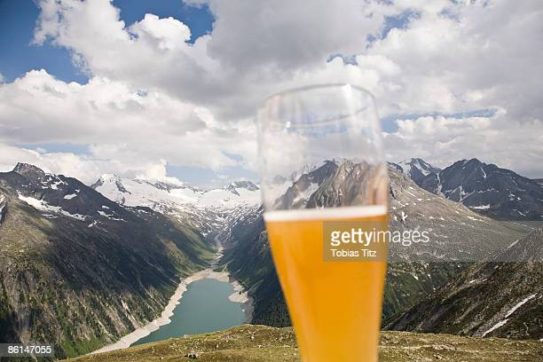 A beer glass in front of a view of the Austrian Alps