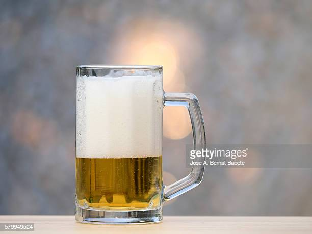 Beer glass to the half, on a table of wood outdoors illuminated by the light of the Sun