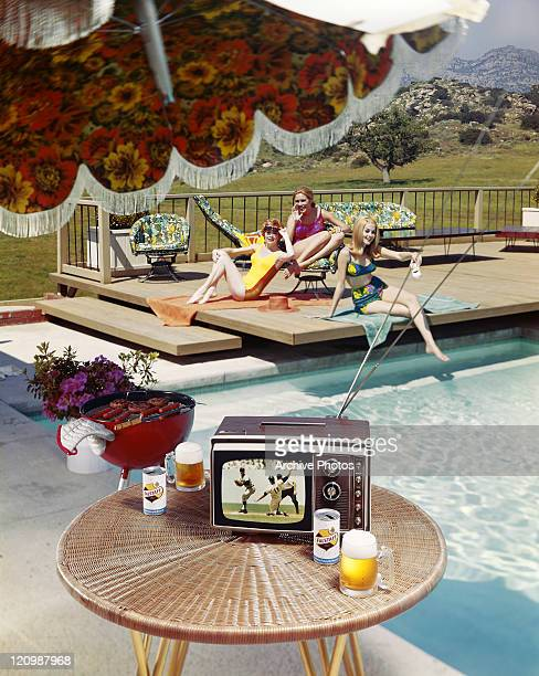 Beer glasses and television on table with friends beside pool in background, smiling