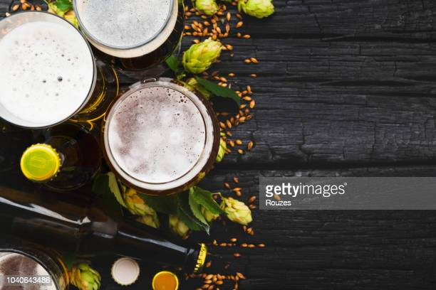 beer in a glass with green hops and space for text. top view - wood table top stock photos and pictures