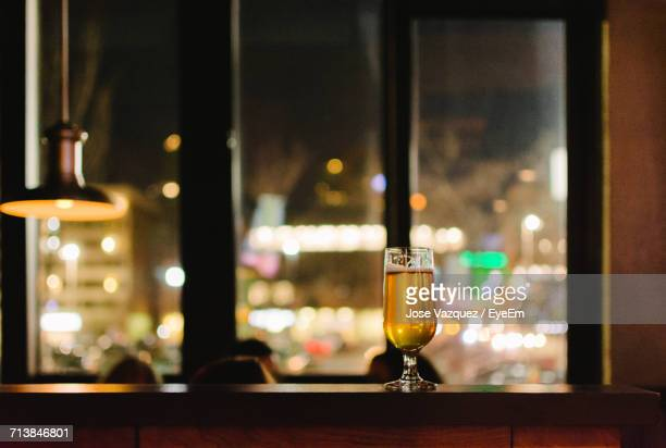 Beer In Glass On Table Against Window In Bar