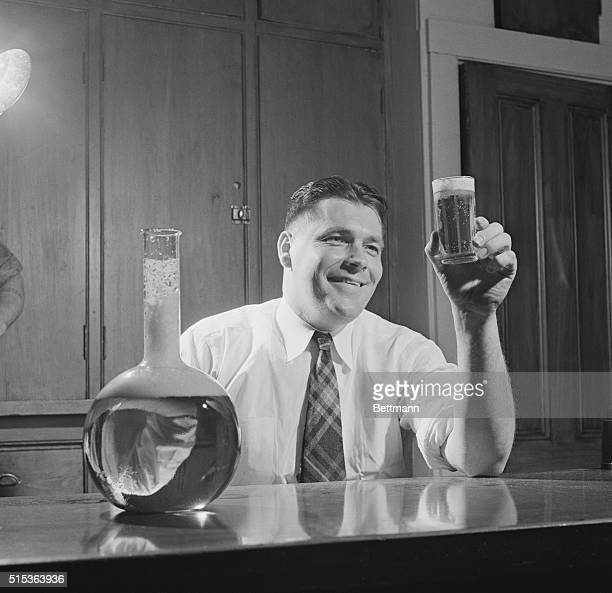 Beer is His Business Portrait of a man happy in his work is Alfred Bowman as he contemplates a sparkling glass of beer The flask at right holds the...