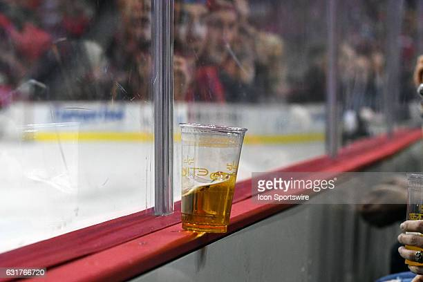 A beer left of dasher board falls over in the first period on January 11 at the Verizon Center in Washington DC The Washington Capitals defeated the...