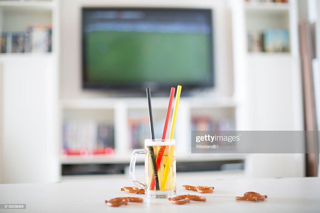 Beer mug with three drinking straws in German national colours and pretzels in front of television with empty soccer field : Stock-Foto