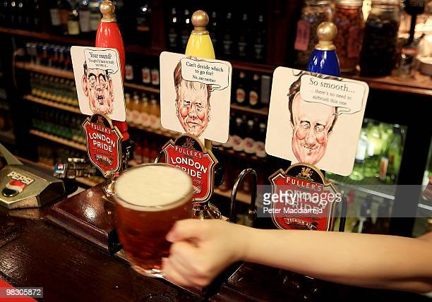 Beer pumps at the Marquis of Granby public house in Westminster display the caricatures of the three political party leaders Gordon Brown Nick Clegg...