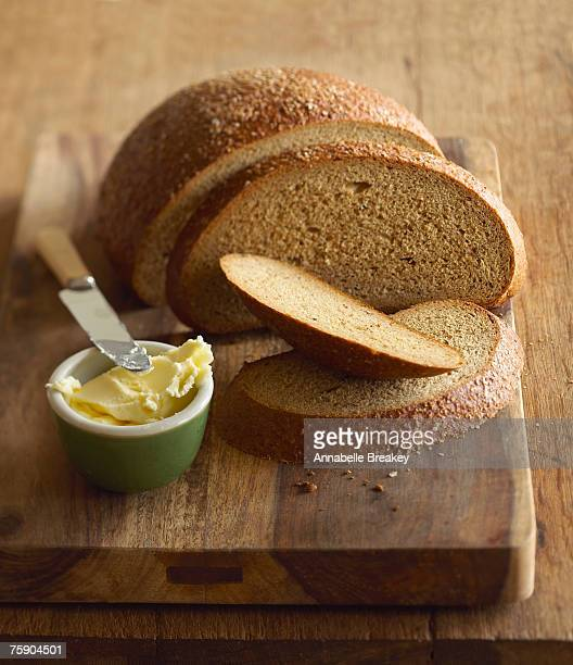 Beer rye bread and butter on chopping board, close-up