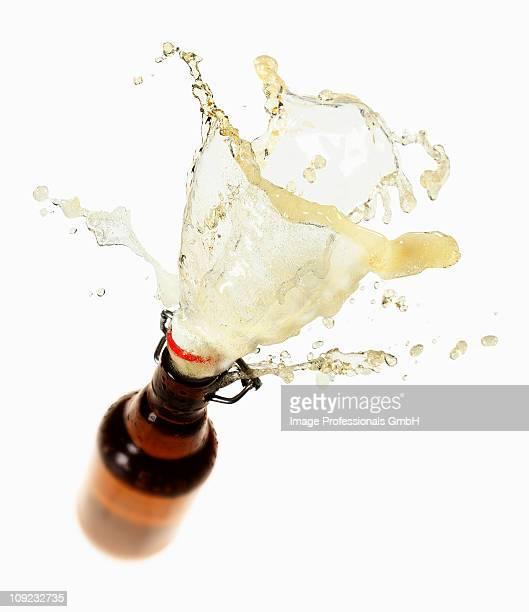 Beer splashing out of brown bottle