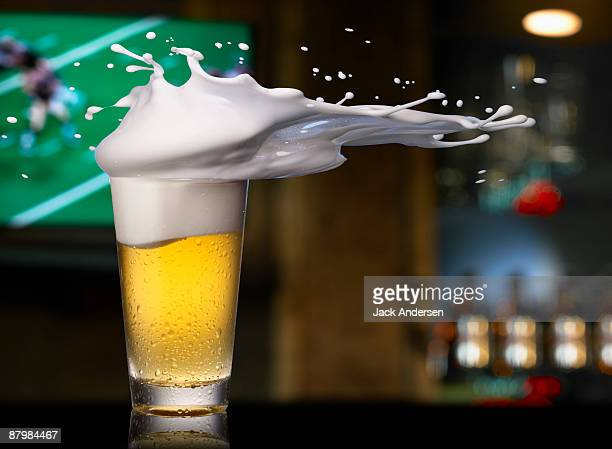 Beer splashing out of pint glass