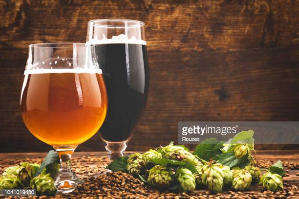 beer surrounded by hops on wooden background