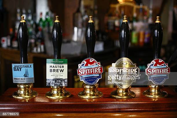 Beer tap badges for Shepherd Neame Plc brewed ales sit on the bar at The Sun Inn in Faversham UK on Friday April 22 2016 Kentish Ale is one of the...