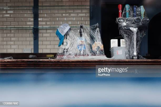 Beer taps stand wrapped in cling film at a shuttered pub in Clapham in the borough of Lambeth in London, England, on April 1, 2020. Official figures...