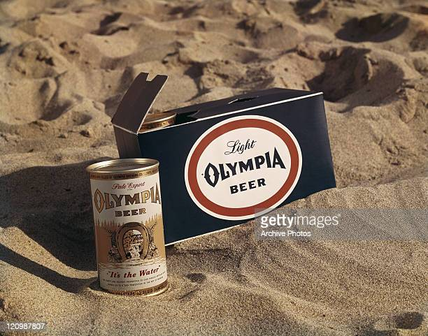 Beer tin and box on sand, close-up