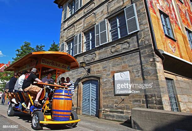 A beerbike at the former City Hall at the river Regnitz with its facade in rococo style on June 11 2009 in Bamberg Germany Bamberg is listed as a...
