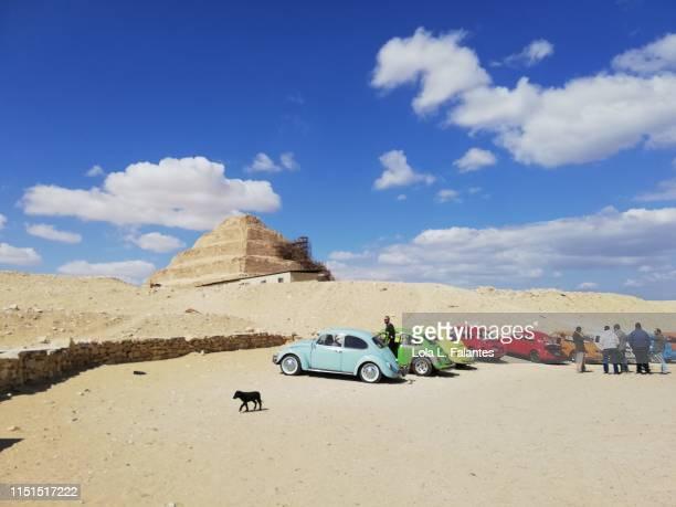 Beetle cars and tourist visiting the  steep pyramid of Djoser. Saqqara.