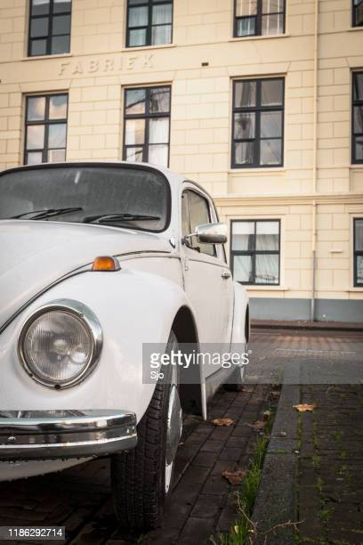 vw beetle or officially the volkswagen type 1 classic car parked in front of an old factory - status car stock pictures, royalty-free photos & images