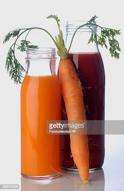 Beetroot and carrot juice in bottle with carrot, close up