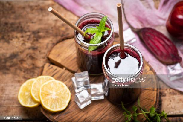 beetroot juice in a glass with ice and lime fruit - juice drink stock pictures, royalty-free photos & images