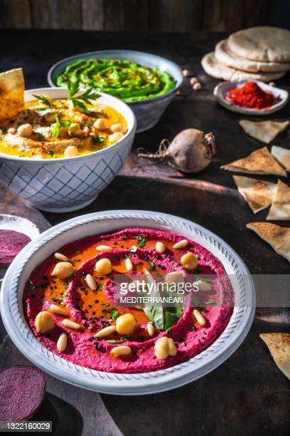beetroot pink hummus bowl closeup with pita flatbread dipping on dark wood table - lebanon country stock pictures, royalty-free photos & images