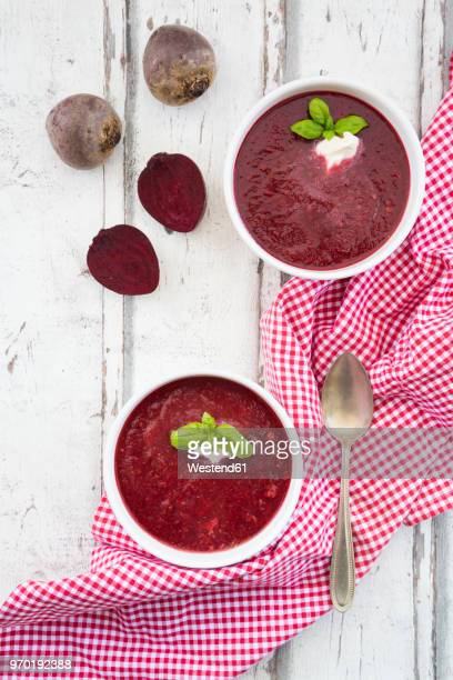 Beetroot soup in bowl on white wood