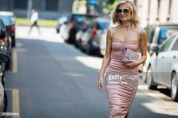 ADONTS before Dolce Gabbana in a DG bag and pink dress during Milan Men's Fashion Week Spring/Summer 2019 on June 16 2018 in Milan Italy