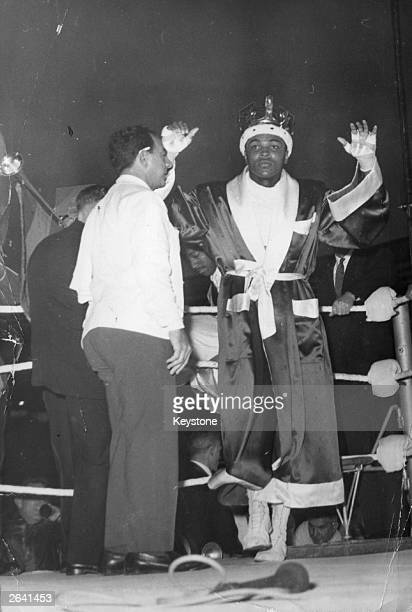 Before his fight with British boxer Henry Cooper at Wembley Stadium American boxer Cassius Clay parades in the ring before the crowd of 55000 wearing...