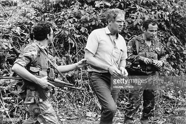 Before his trial American prisoner Eugene Hasenfus is led by two Sandinista guards to the place where his plane was shot down