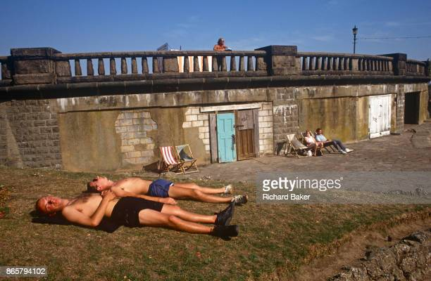 Before the area was completely redeveloped with a pleasure fairground 1990s sunbathers stretch out on bare grass on the seafront that still shows its...