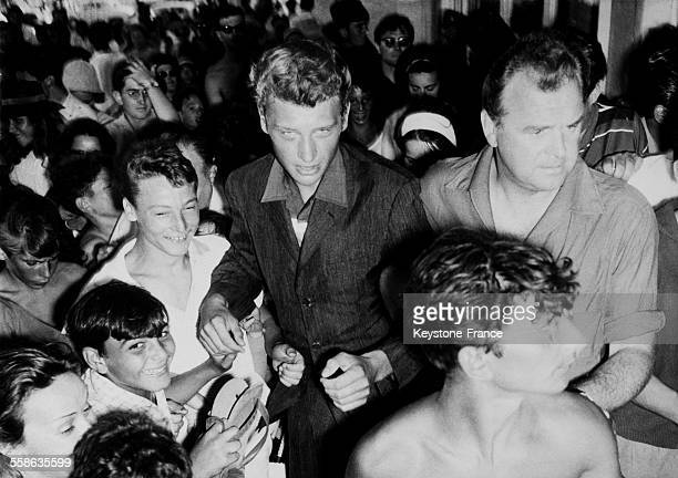 Before the closed doors of the Palais du Festival Johnny Hallyday dancing the twist At his side his impresario Johnny Stark in Cannes France on...