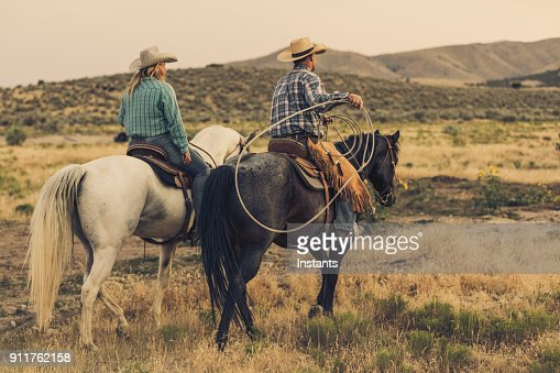 Before the run of the horses begins, a cowgirl and a cowboy, who is holding a lasso, are both sitting on their horses.