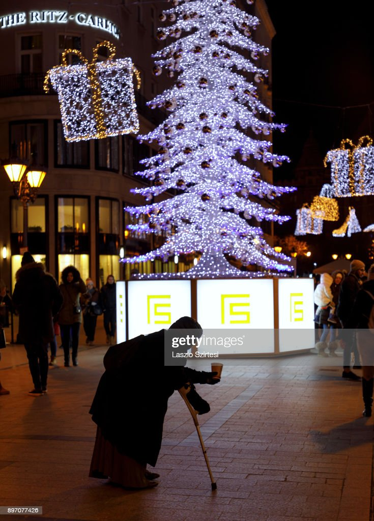 A beggar asks for alms among Christmas decorations at 'Fashion street' on December 19, 2017 in Budapest, Hungary.