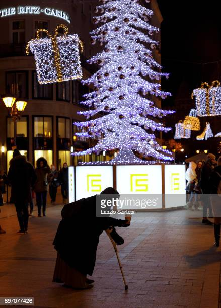 A beggar asks for alms among Christmas decorations at 'Fashion street' on December 19 2017 in Budapest Hungary