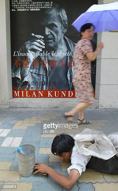 A beggar creeps under a poster promoting the wellknown Crech writer Milan Kundera's work The unbearable lightness of being as a pedestrian walks past...